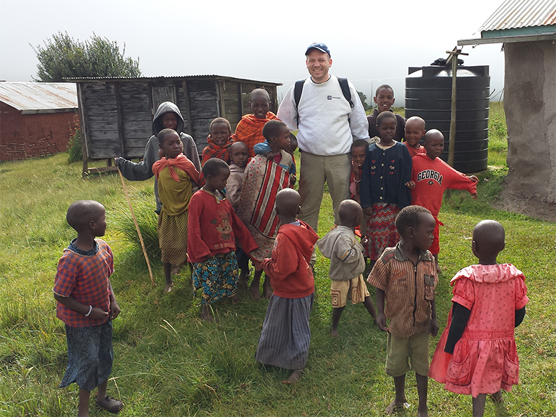 Matt Maloney with Maasai children in front of a waterbarrel we installed