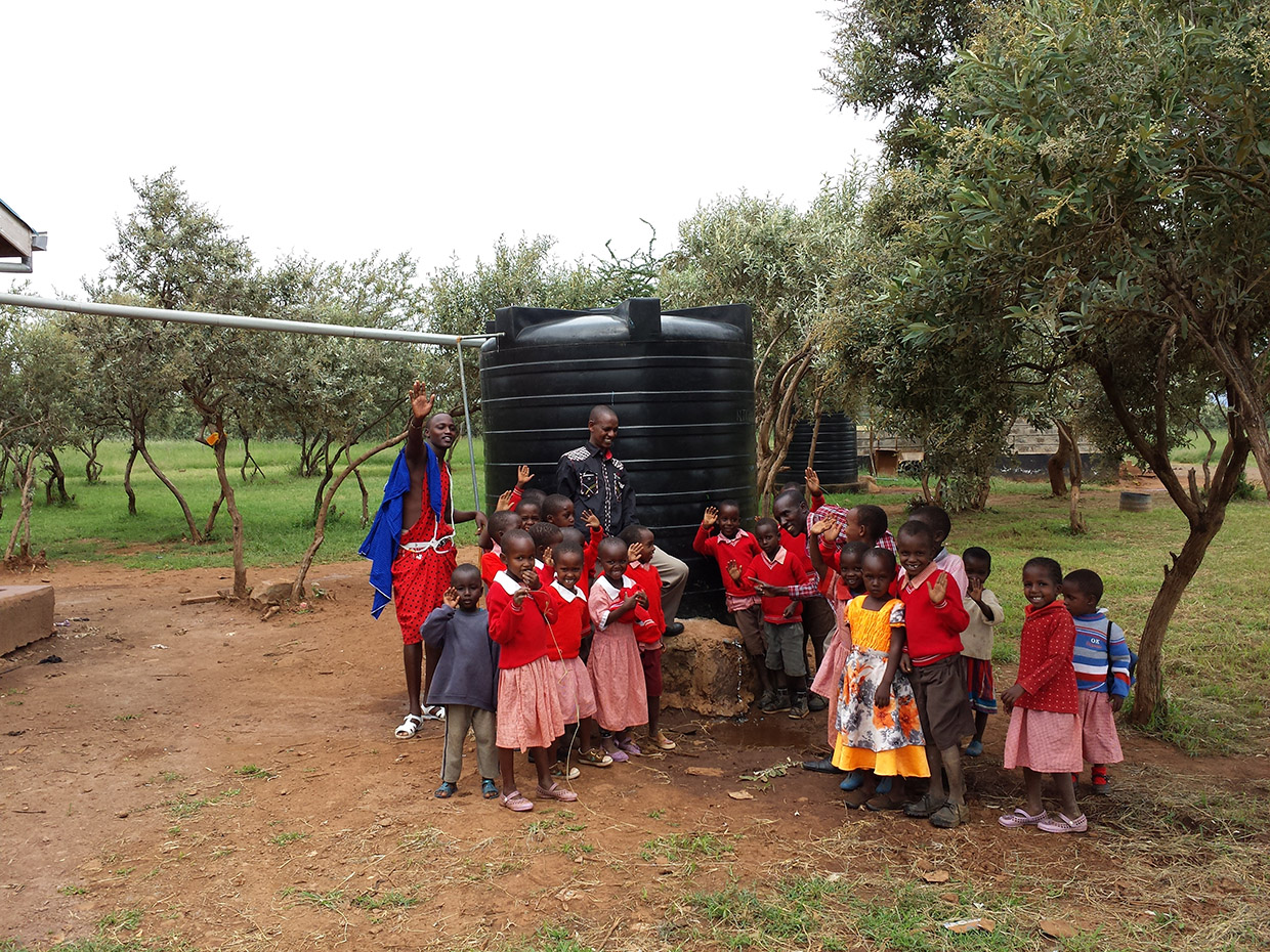 Children and Salomon posing in front of the third rainbarrel installed